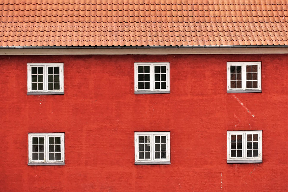 The image shows the photograph of a red house facade with six white windows an par of the roof.