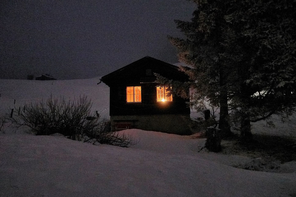 The image shows the photograph of a small mountain cabin in a winter landscape by night. The lights are on inside the cabin.