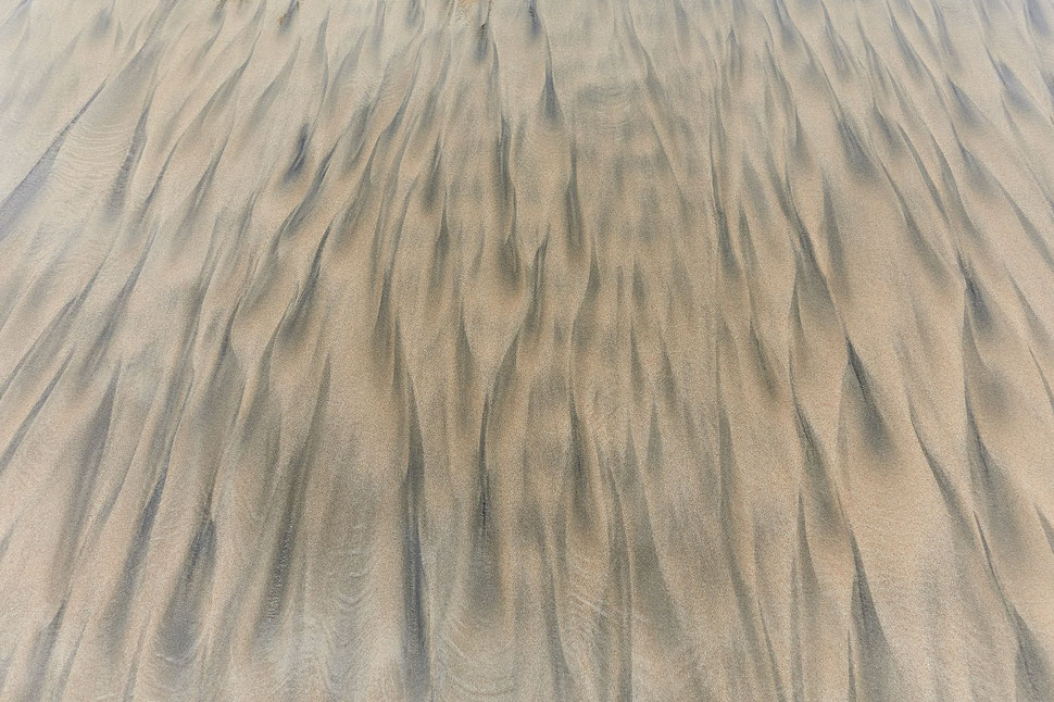 The images shows the photograph of sand structures and patterns on a beach in Ghana.