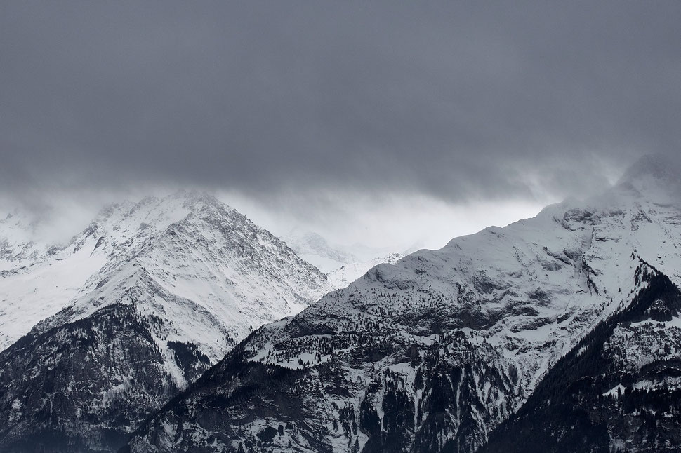 The image shows the photograph of a mountain range that is partly covered by clouds.