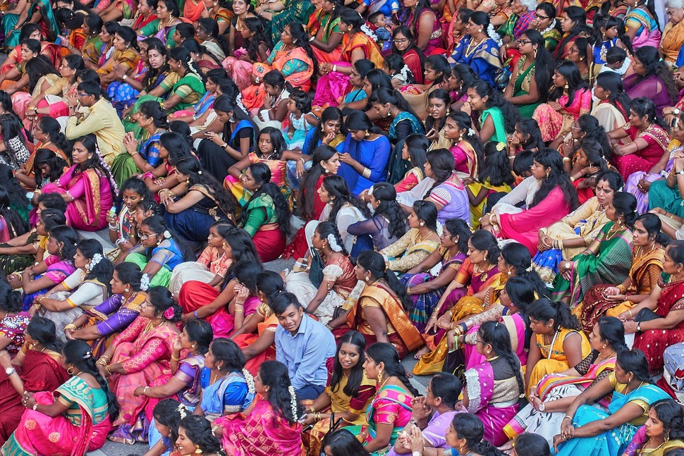 The image shows the aerial photograph of a large crowd of people in colorful dresses celebrating a hindu holiday.