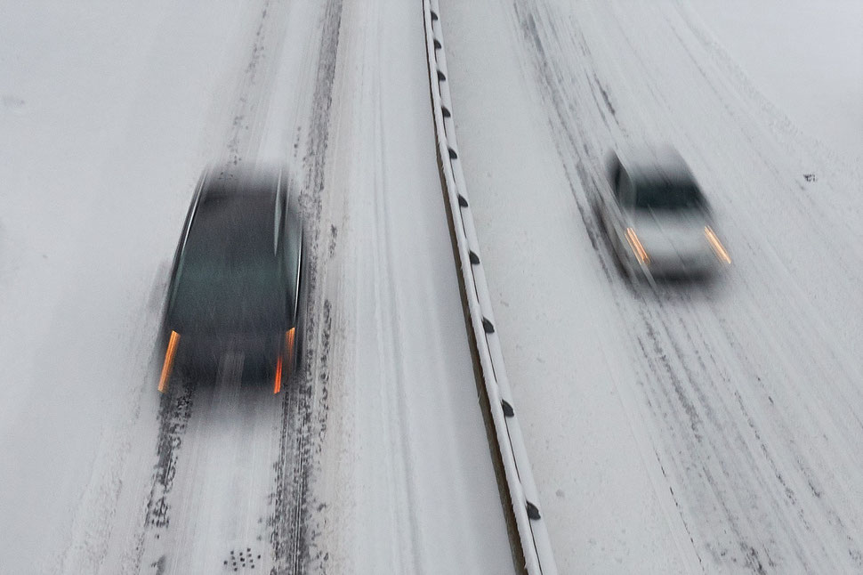 The image shows an aerial photograph of two cars moving in opposite directions; the road is divided by a guard rail.
