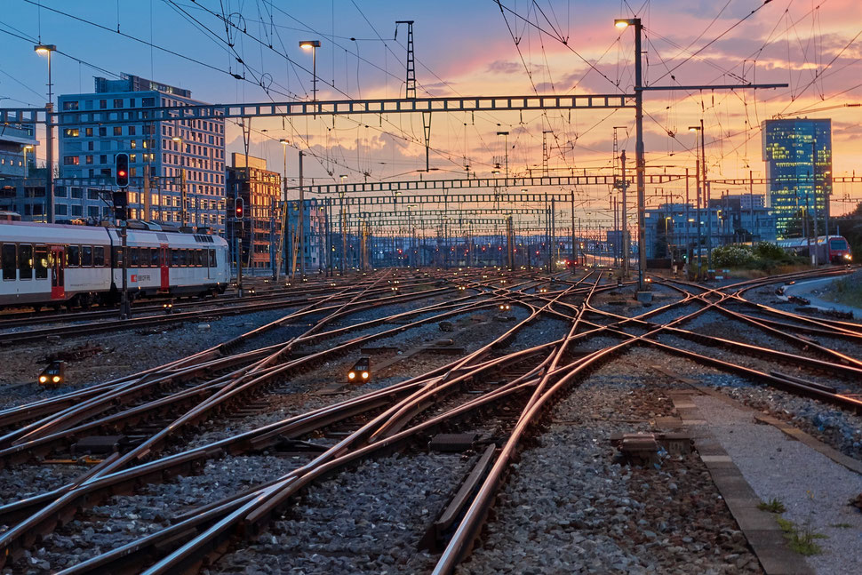 The image shows a photograph of main train tracks, building and train compositions at Zurich Main Station while the sun is setting.