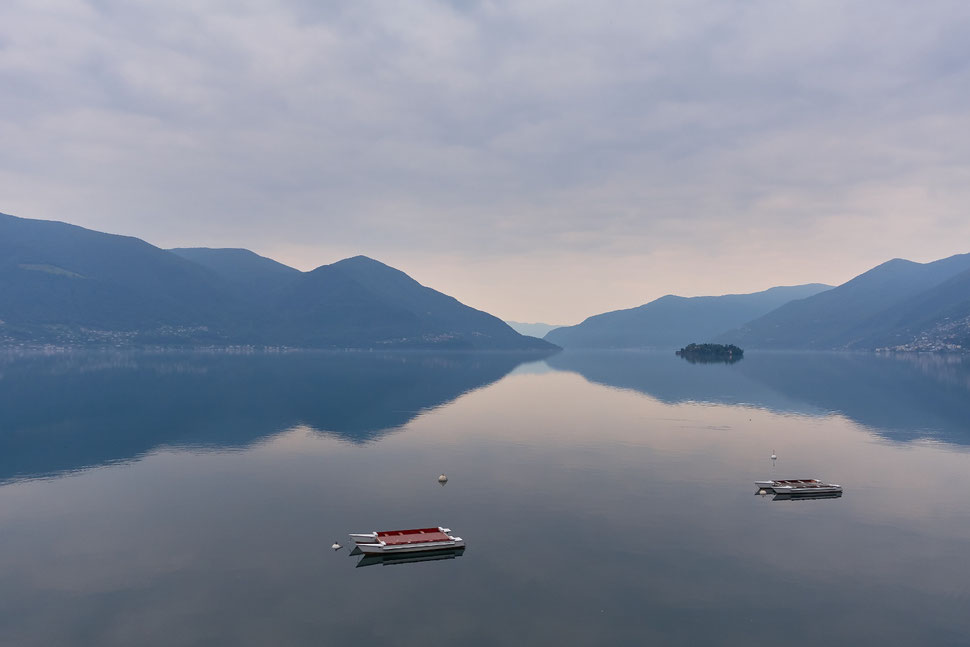 The image shows the photograph of a part of Lake Maggiore with one of the Brissago islands and the shore with mountains. The water is very still and there are two bathing rafts in the foreground.