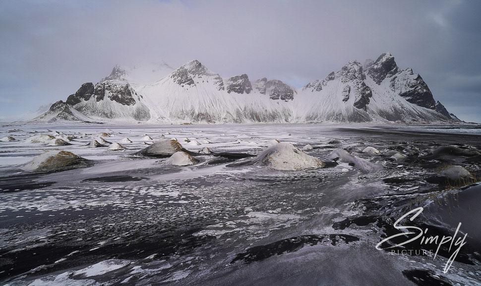 Iceland, Strand mit kleinen Hüheln und grossen Bergen im Hintergund, alles ist verschneit