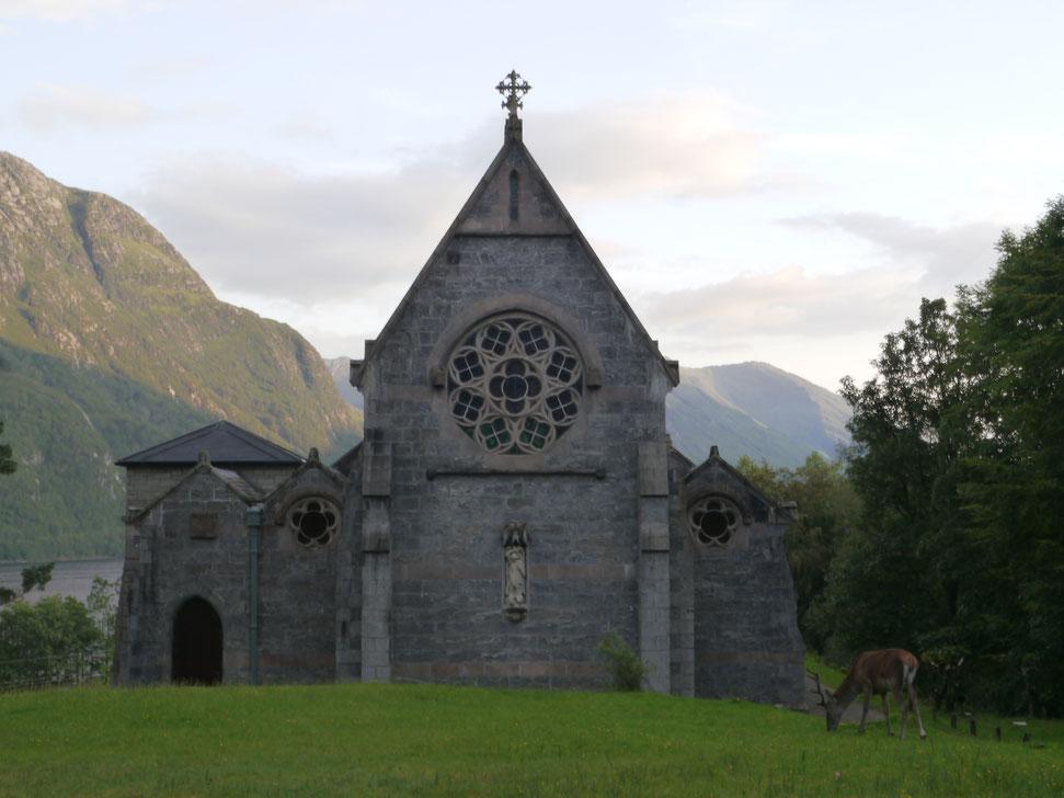 Kleine Kapelle in Glennfinnan im Abendlicht mit Hirsch davor