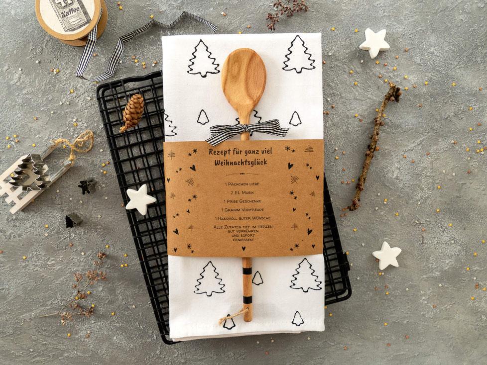 Weisses Küchentuch mit schwarzen Tannenbäumchen gestemptelt. Papier Banderole mit aufgedrucktem Rezept für Weihnachtsglück