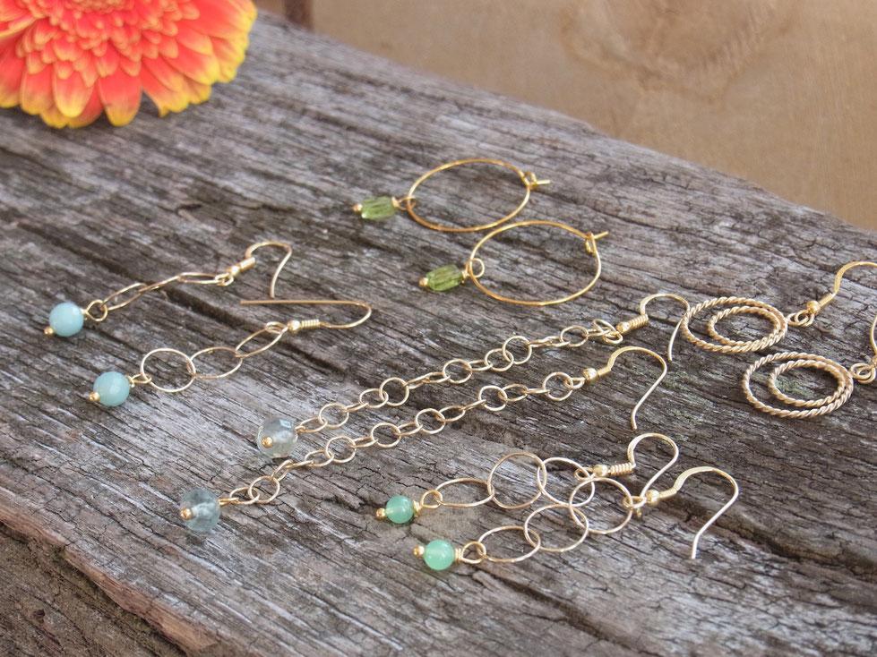 Goldene Ohrringe mit Edelsteinen wie hellblauer Amazonit, grüner Peridot