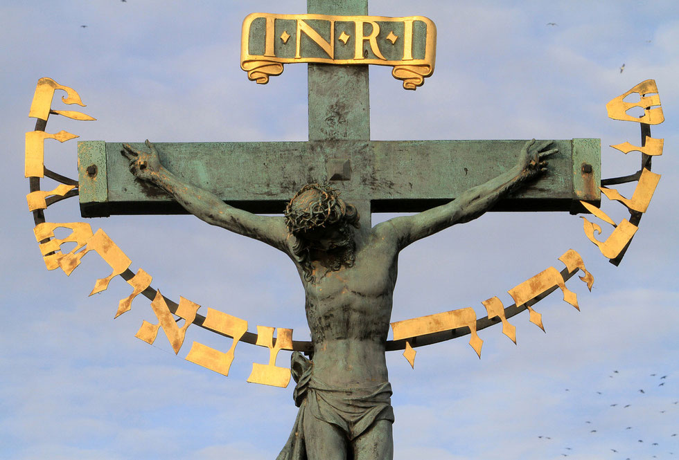 Crucifix and calvary on Charles Bridge. Statue of Jesus on the cross with Hebrew lettering. Prague.