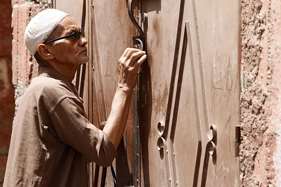 Sénior marocain fermant la porte de son domicile. Marrakech.