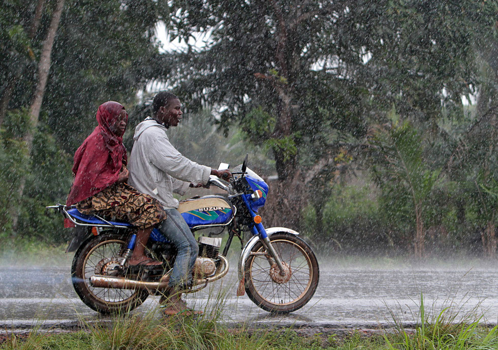 African motorists traveling couple Beninese motorcycle in the rain. Ouidah.