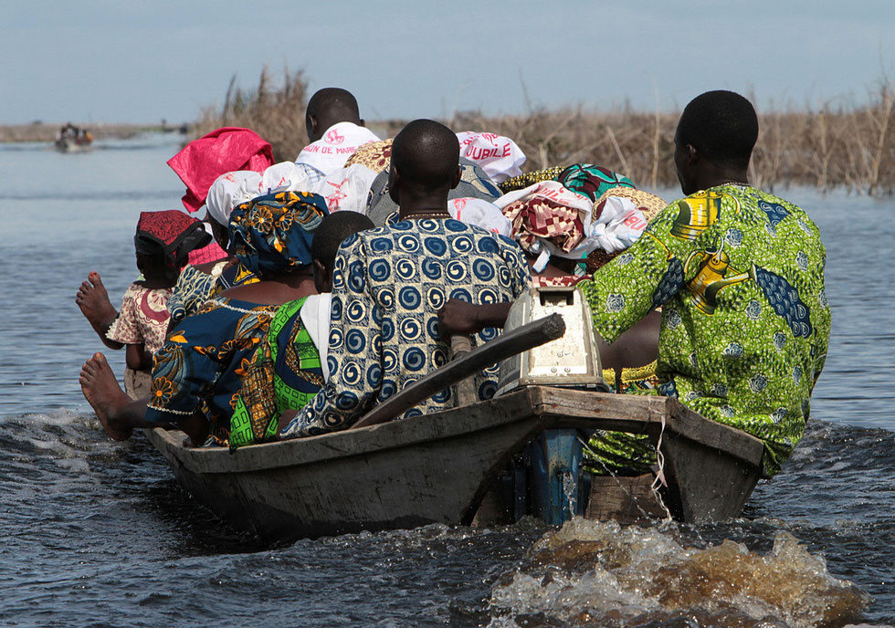African transporting equipment on a boat. Lake Nokoue. Ganvie.