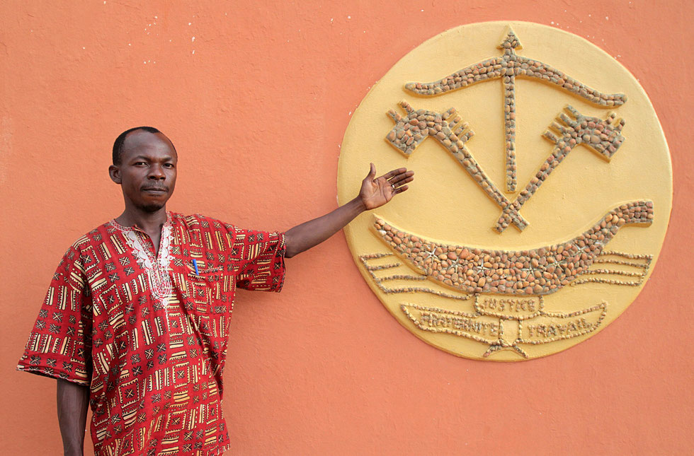 African man shows a mosaic of ink and a boat. The Door of No Return. Ouidah.
