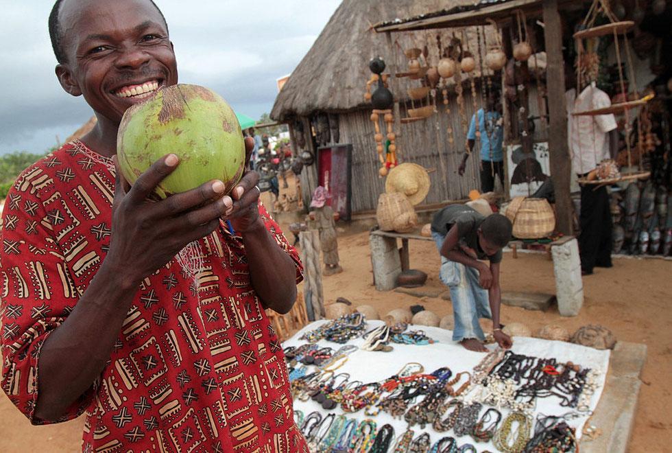 Afrique de l'Ouest, Afrique, Bénin, Ouidah, extérieur, avec personnage, adulte, homme, Africain, Béninois, alimentation, aliment, nourriture, fruit, noix de coco, marché, commerce, sourire, geste, manger, soif