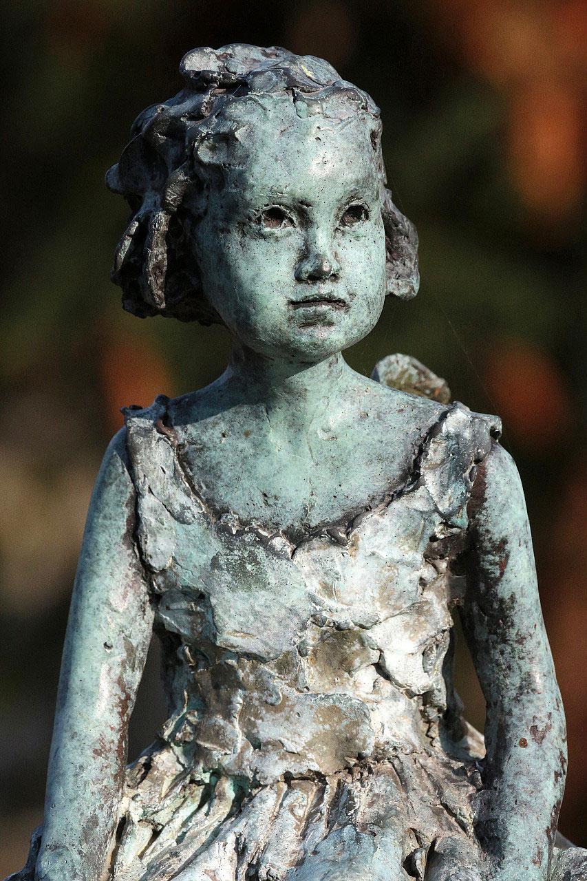 Figurine en bronze assise sur une pierre tombale. Cimetière Père Lachaise.