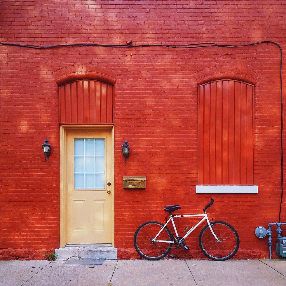 vélo stationné devant une maison rouge
