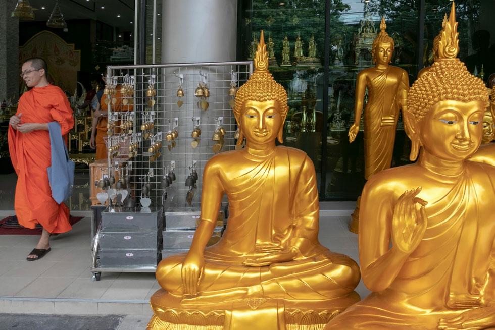 Vienuolis prie budistinių reikmenų parduotuvės