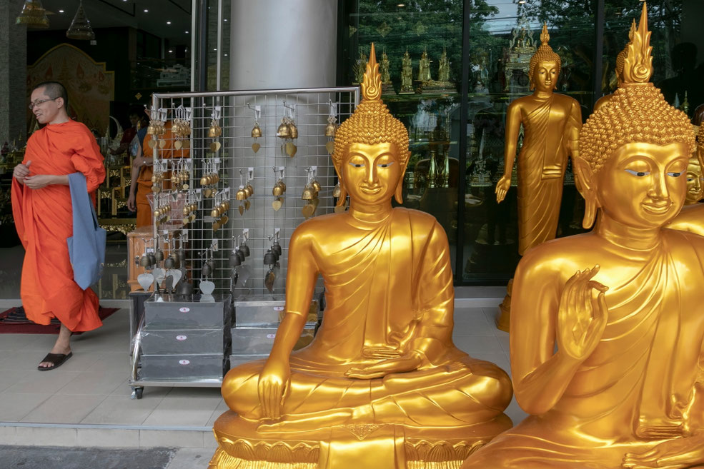 Budistų vienuolis prie ritualinių reikmenų parduotuvės Bankoke