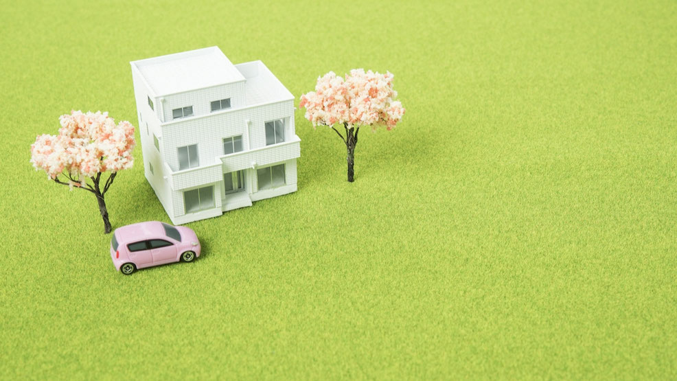 緑の芝生の上に置かれたミニチュアの家と桜の木と車