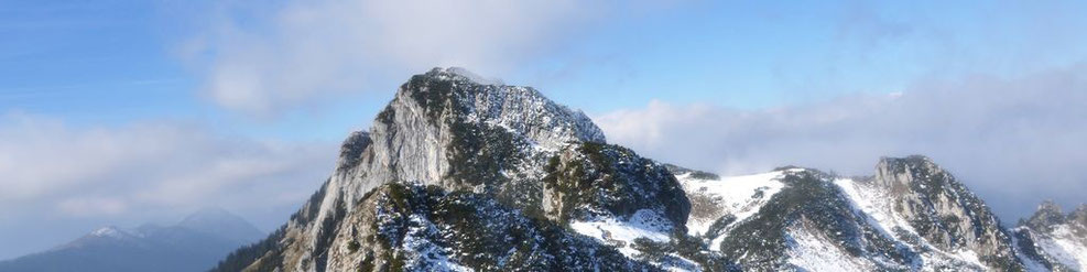 Leicht verschneiter Berggipfel der Benediktenwand mit abziehenden Wolken
