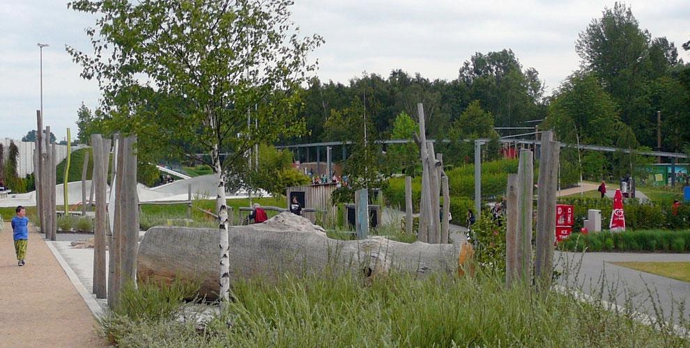 Eingebettet in Gräser und wogende Stauden liegt die Sitzecke aus Baumstammbänken geschützt, aber mit guter Übersicht über die Bewegungswelt!