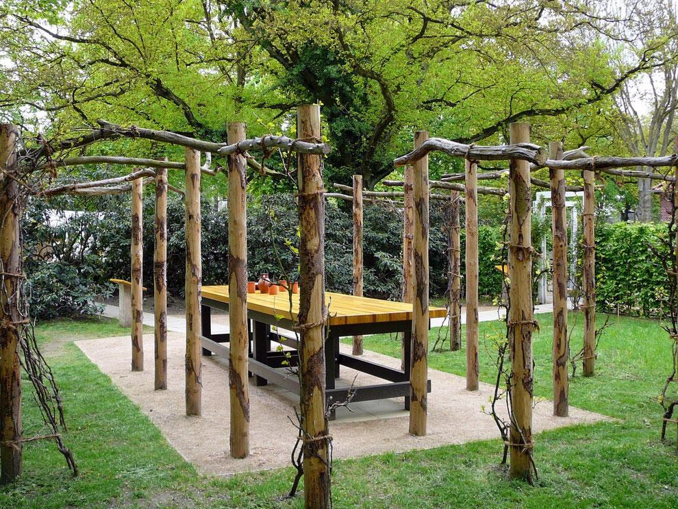 Um diesen Tisch versammelt man sich gerne; er wurde aus Holz-Spenden verschiedener Gemeinden zusammengesetzt. Daneben eine Tafel mit dem gemeinsamen Gebet, dem Vaterunser in vielen Sprachen