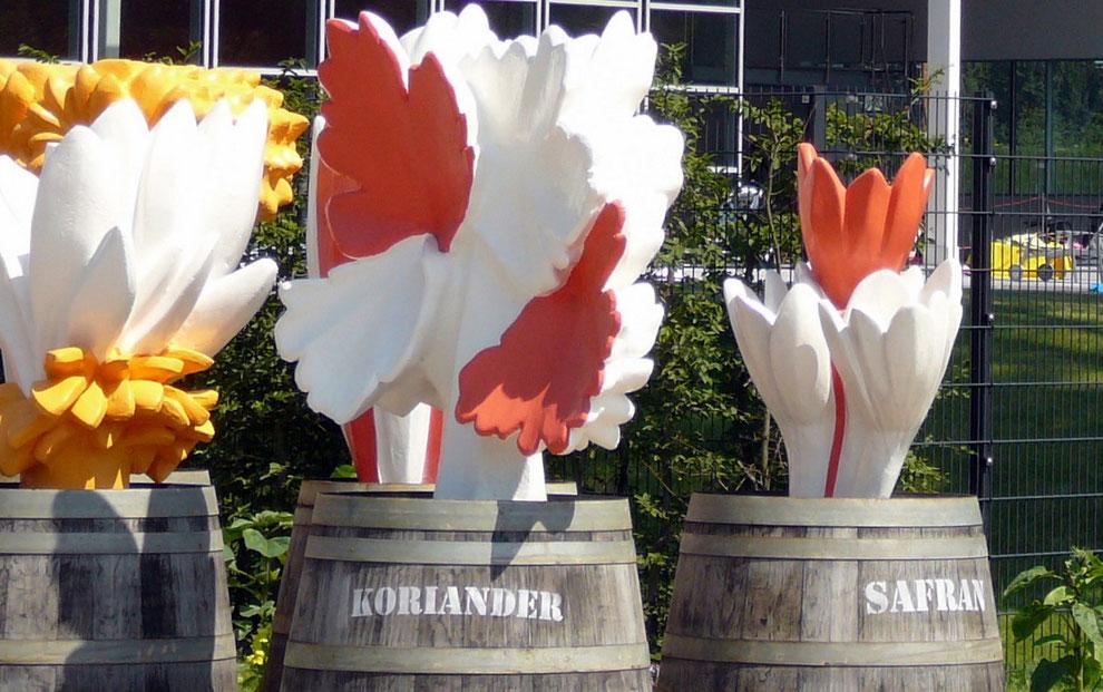 Gewürz-Fässer mit Riesen-Gewürz-Blüten warten am Kanal auf den Weitertransport