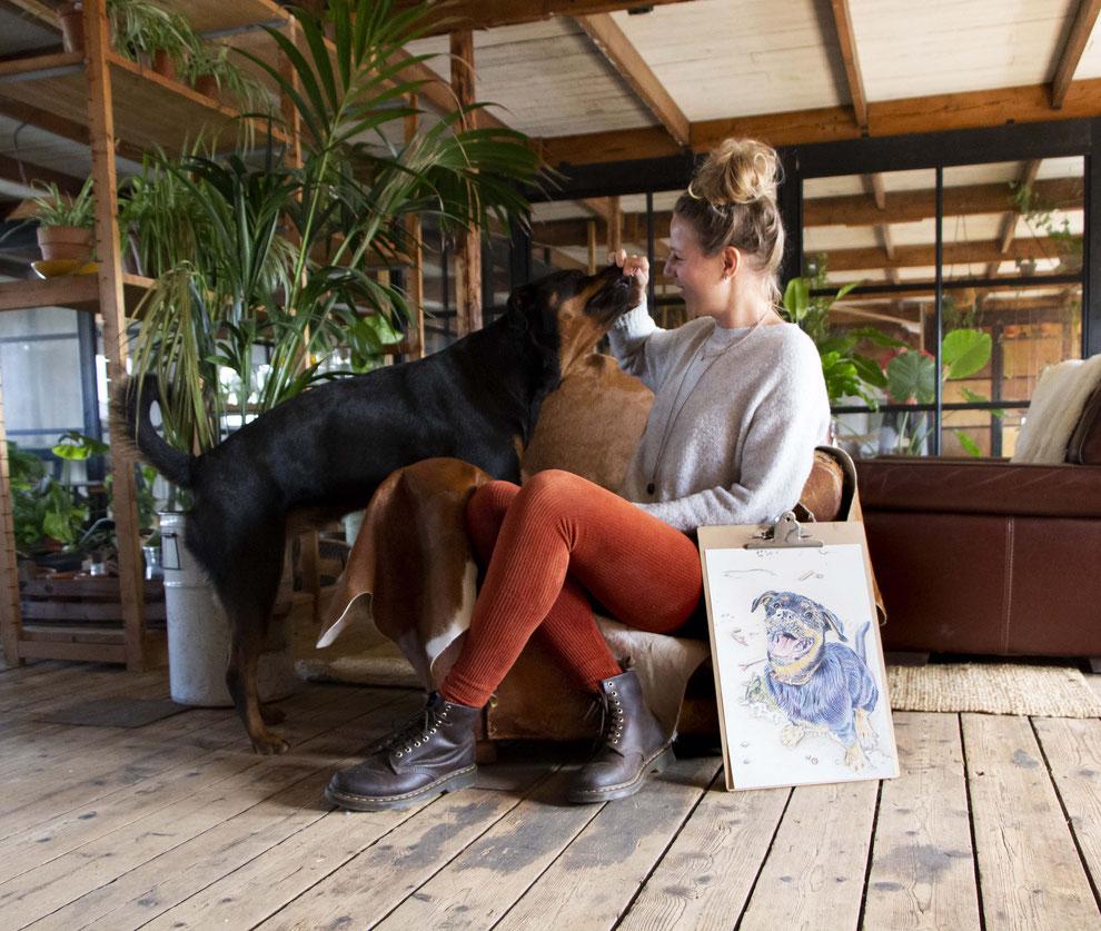 Een jonge dame zittend op een stoel, geeft een snoepje aan een rottweiler. Naast de stoel staat een tekening van de hond op een klembord.