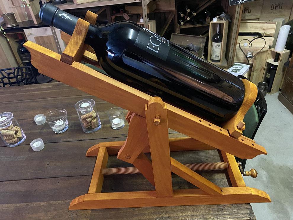 Wein dekantieren mit einer Weinwiege aus Holz.