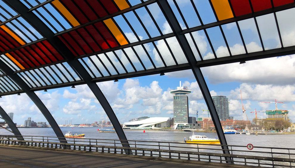 Blick vom Hauptbahnhof (Amsterdam Centraal) auf das IJ, das Filmmuseum Eye und den Amsterdam Toren