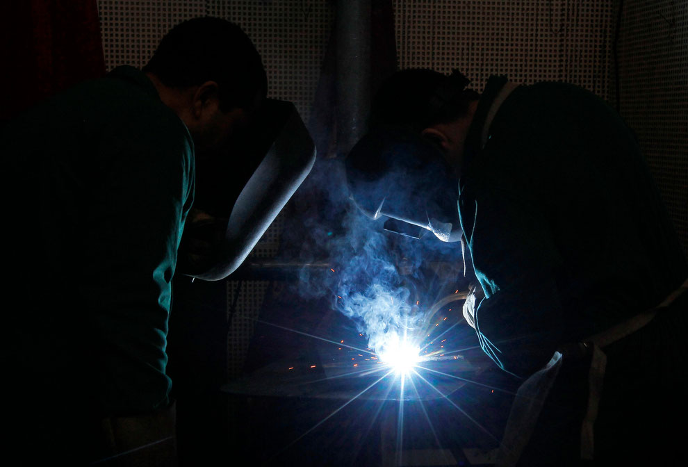 Teacher (L) watches his pupil welding during a practical classroom at the vocational training center of IEFP in Setubal February 1, 2013.