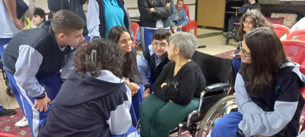 Femme handicapée en fauteuil roulant et élèves sensibilisées