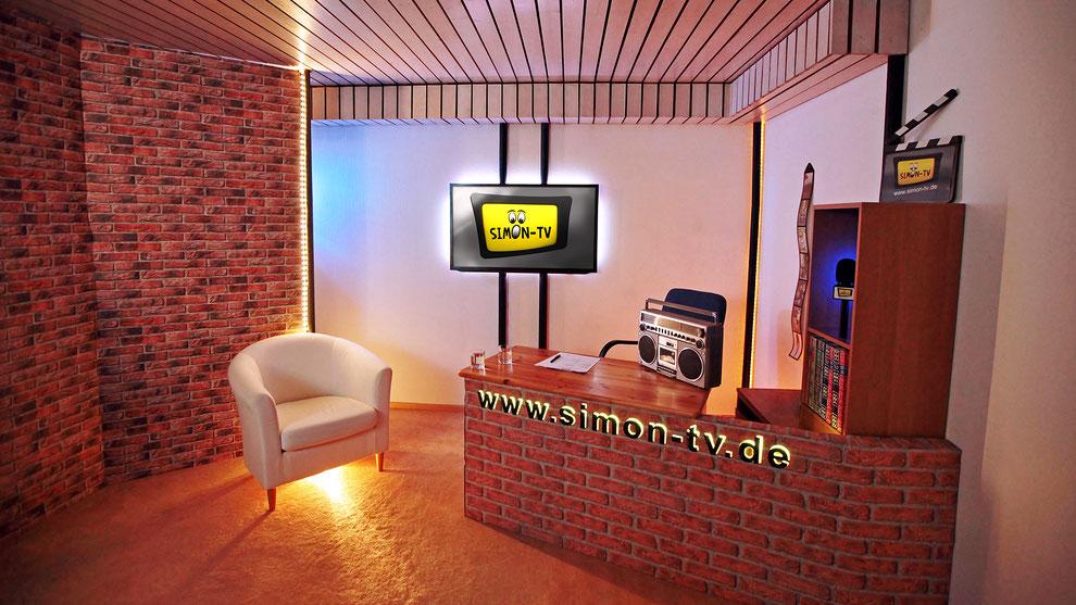 Das selbstgebaute SIMON-TV Studio aus Pappe, Tapete und Baustrahlern.