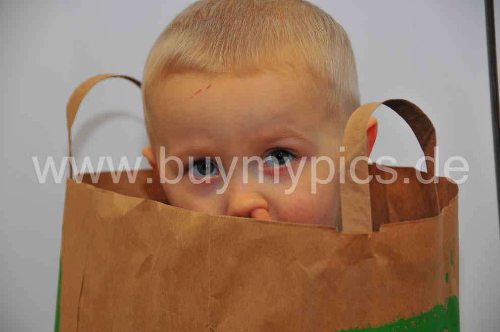 Blick in die Kamera, Kleines Kind popelt in der Nase herum, Fotograf hat das Kind genau erwischt, Kinderfotos