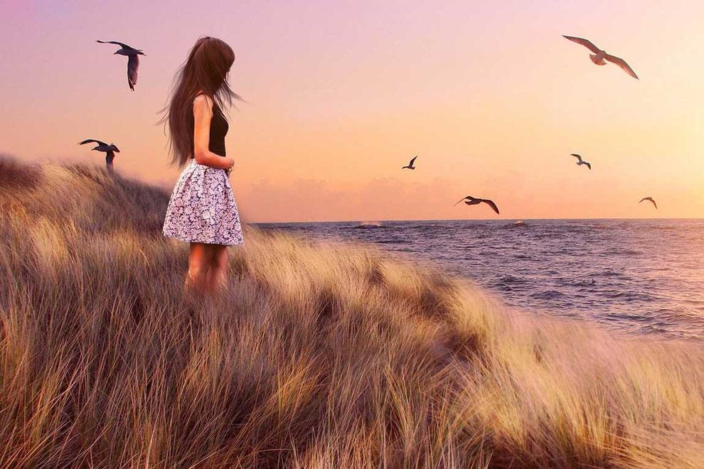 Eine junge Frau steht auf einer mit Gräsern bewachsenen Düne am Meer