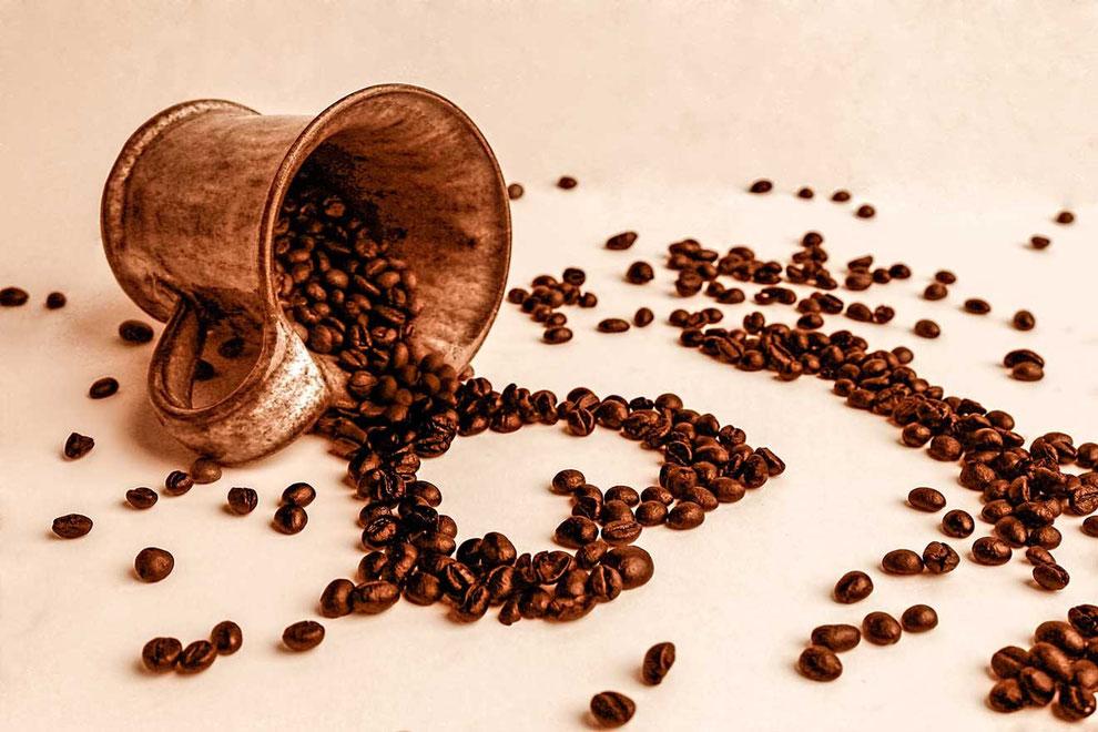 Zahlreiche Kaffeebohnen fallen aus einer Tontasse und formen ein Herz