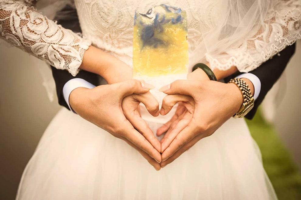 Ein Brautpaar gestaltet mit ihren Händen ein Herz und auf diesem liegt eine Handseife
