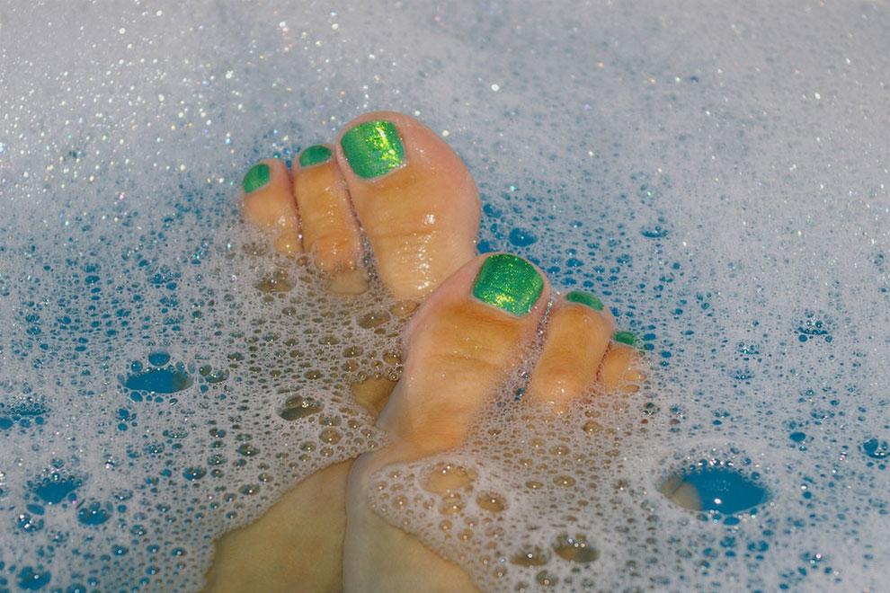 Zwei Füsse einer Frau schwimmen im Schaum des Badewassers