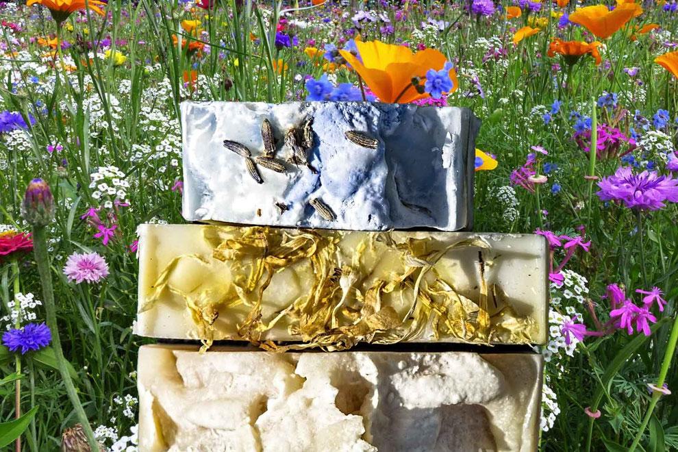 Drei Naturseifen in einer Blumenwiese