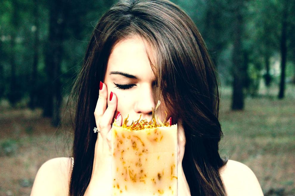 Langhaarige, schöne Frau riecht an einer Naturseife, die als Duschseife verwendet wird