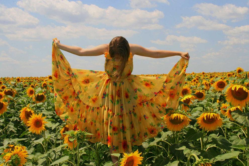 Naturverbundene Frau in einem Feld voller Sonnenblumen
