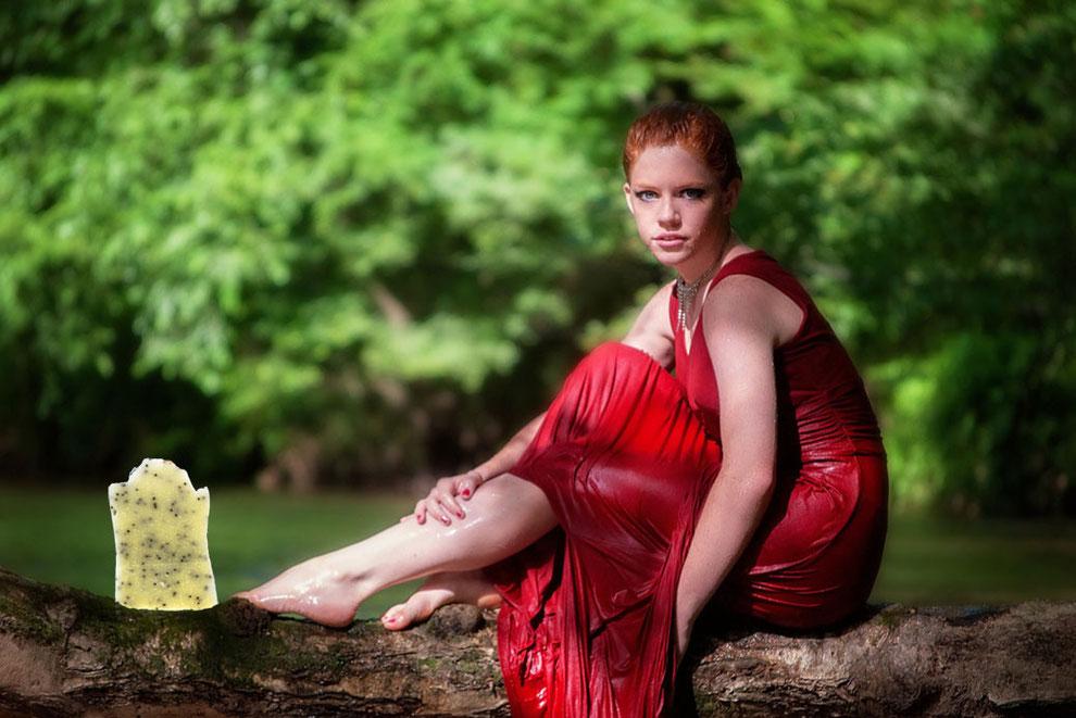 Junge Frau sitzt zusammen mit einer Naturseife auf auf einem Baumstamm am Fluss.