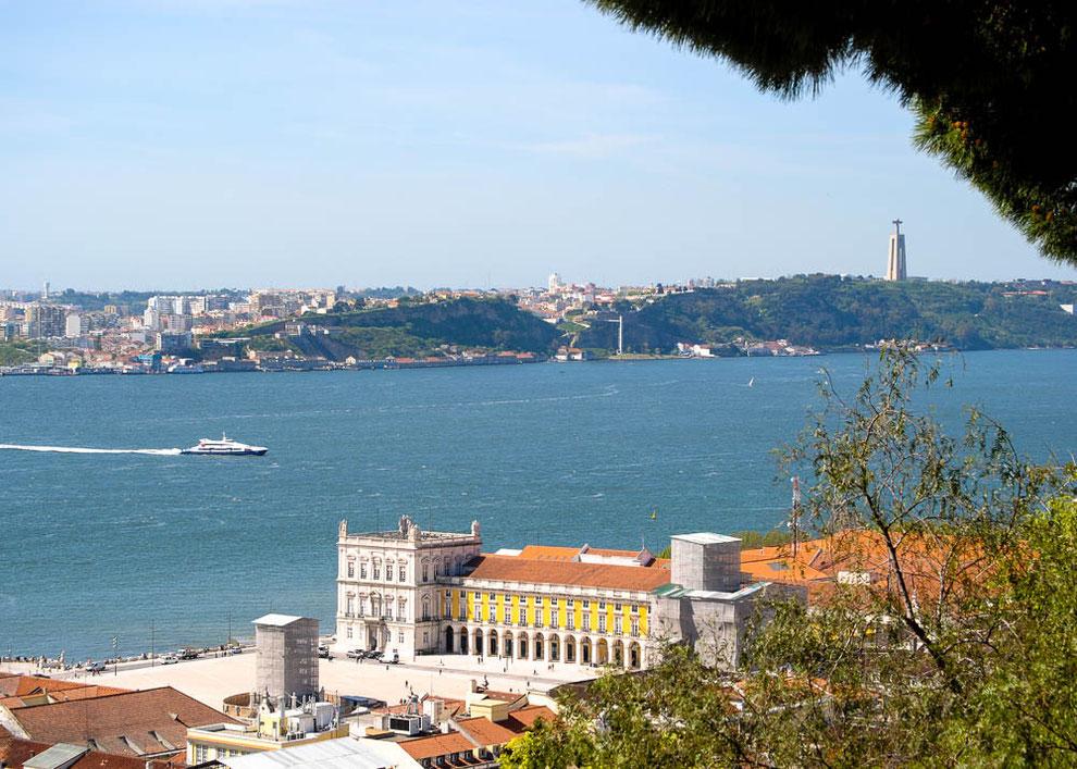 Blick auf Almada mit der Christus Statue. Im Vordergrund der Praca do Comercio, umrahmt von den wichtigsten Ministerien