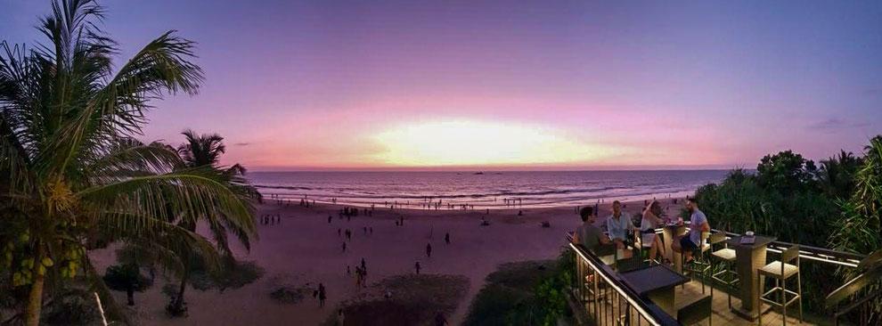 By-by Sri Lanka 2019. Strand mit violettem Sonnenuntergang und einer Baar mit Leuten im Vordergrund. Palmen links und rechts umranden das Bild.