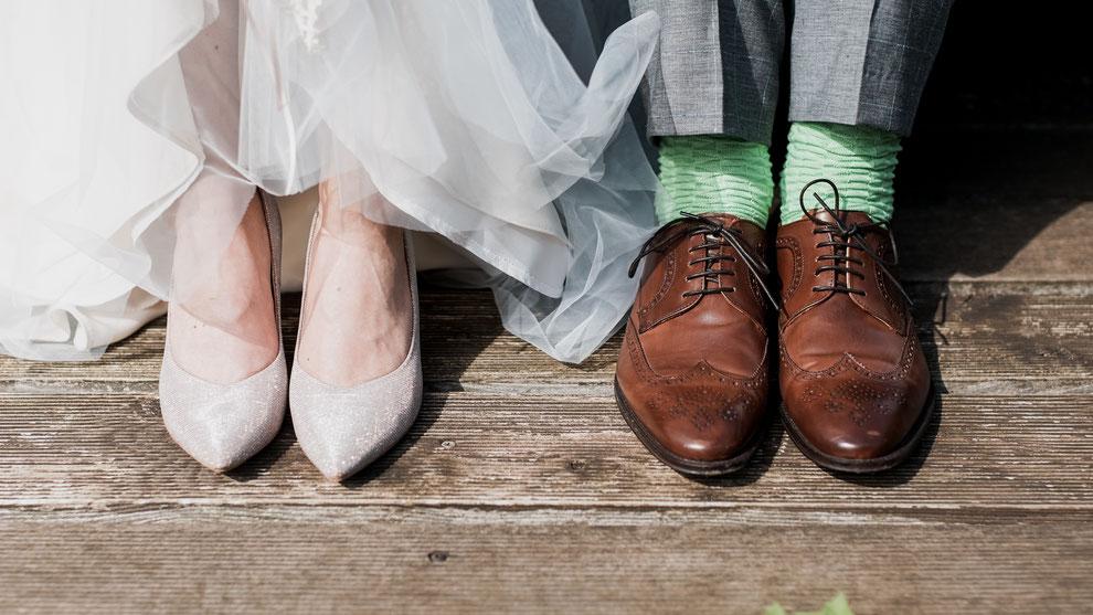 Füsse eines Hochzeitpaares. Sie trägt silberweisse Schuhe und er welche aus braunem Glattleder mit grünen Socken.