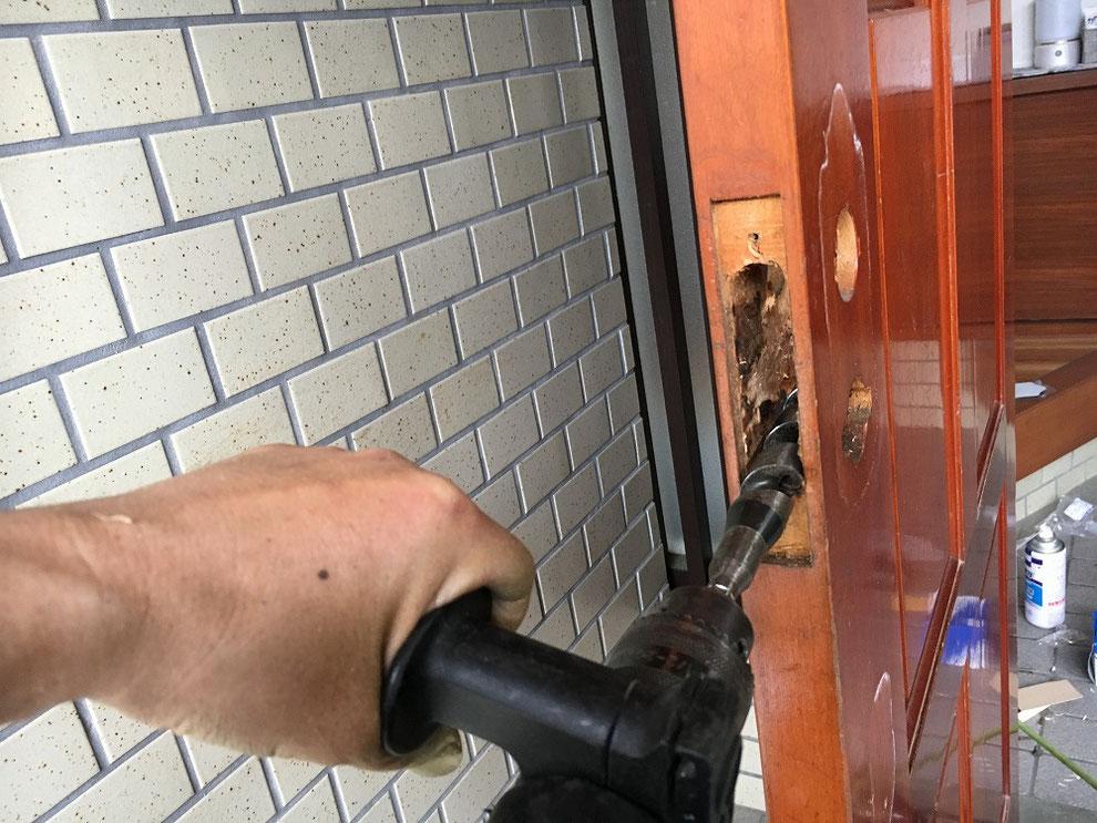 取り替え用サムラッチ錠用に穴を広げているところ