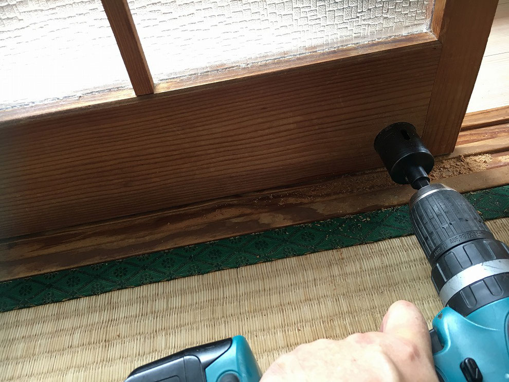ガラス付き引戸に穴をあけているところ