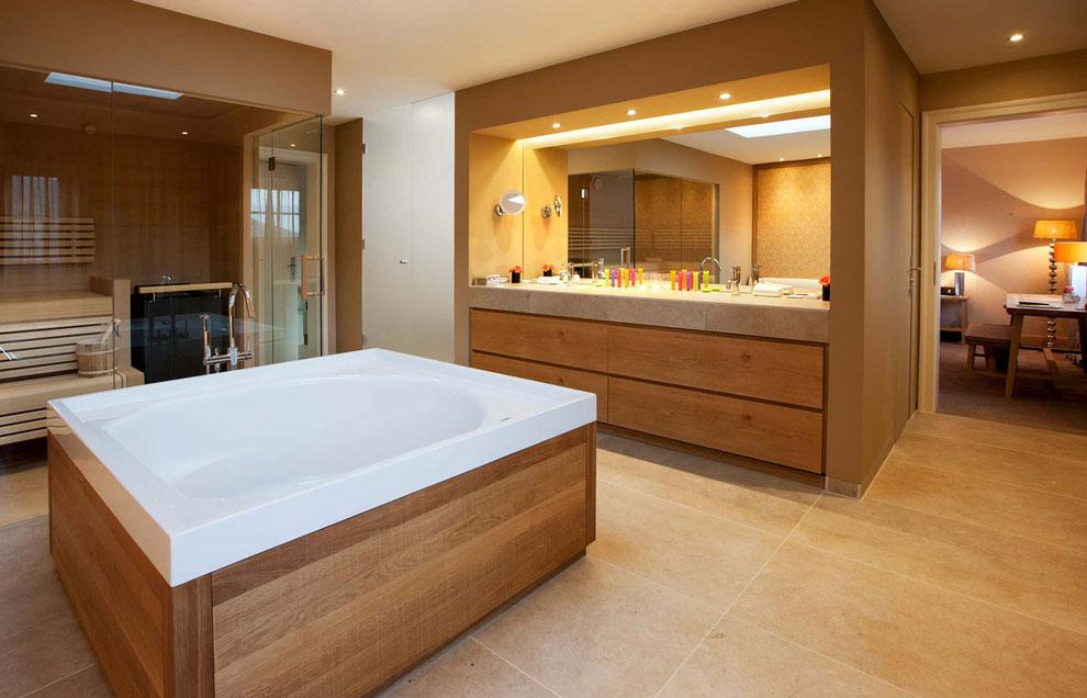 Badezimmer in einer Suite mit Sauna, Badewanne mit Verkleidung aus Massivholz, Waschtisch Eiche Echtholz-Furnier