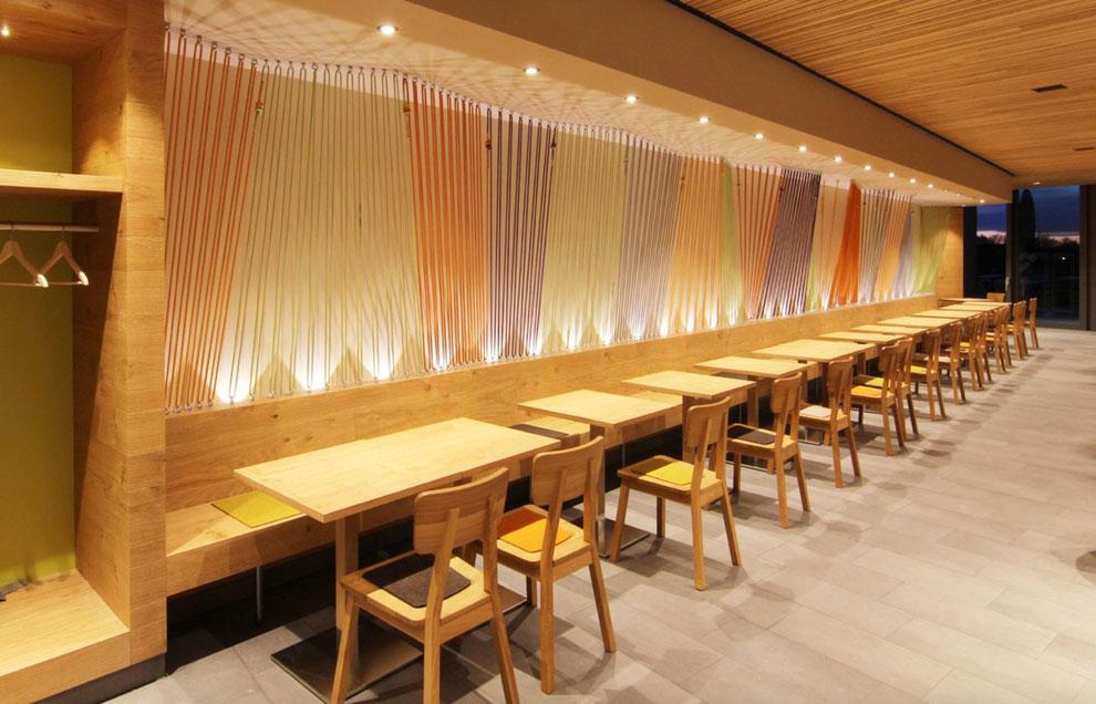 Lange Holzbank mit Stühlen, kleine Tische, dekorative Lichtwand mit bunten, gespannten Seilen im Restaurant