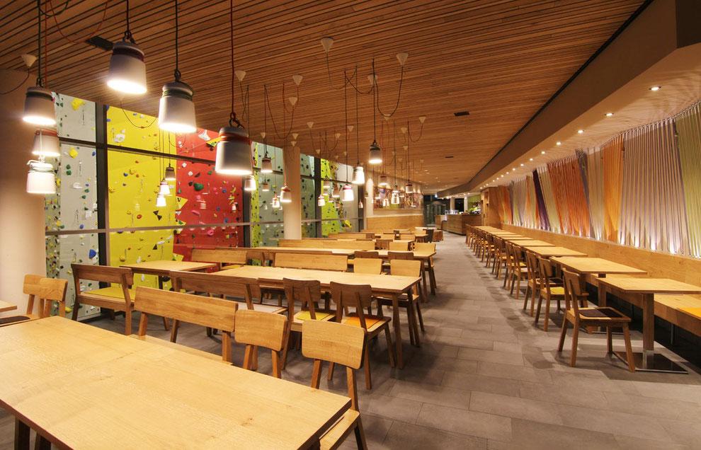 Restaurant mit Glaswänden, Blick auf Kletterwand, Möblierung Eiche massiv und Echtholz-Furnier, farbiger Schichtstoff, dekorative Elemente